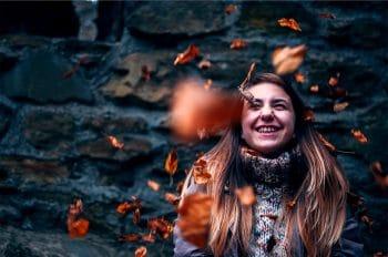 naurava nuori nainen hymyilee iloisena ja syksyn lehdet putoilevat päälle