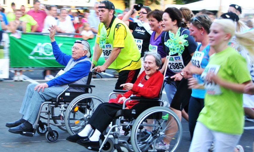 vanhukset ja muut juoksukilpailussa pyörätuolissa