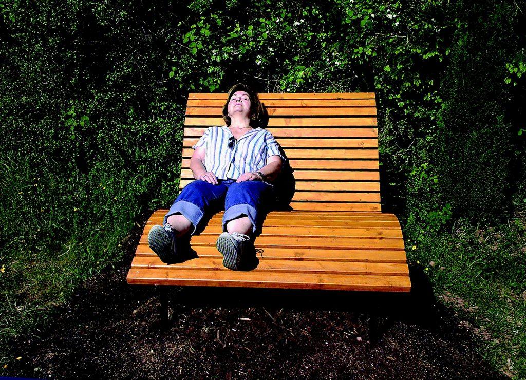 nainen istuu penkillä auringonpaisteessa silmät kiinni