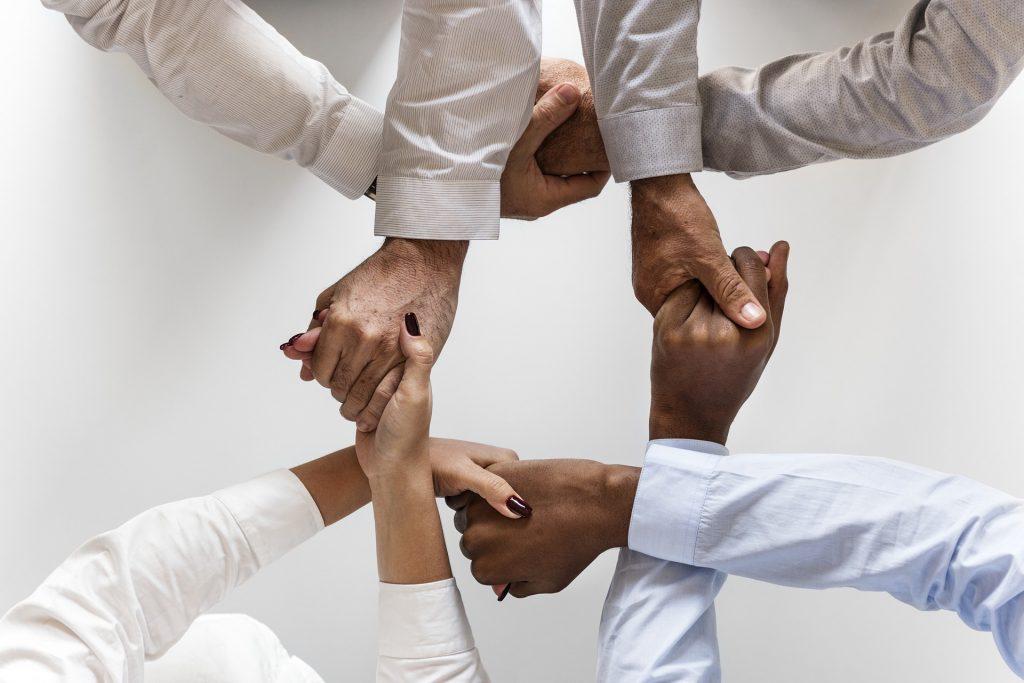 Monta ihmistä pitää käsistä kiinni, kuvastaen yhteistyötä