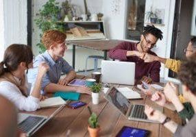 Monta ihmistä työpöydän äärellä lyöden nyrkit yhteen onnistumisen merkkinä.